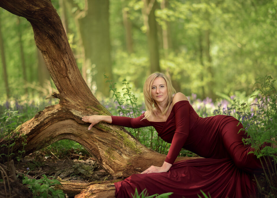 woman wearing red dress posing on a tree trung outdoor photoshoot in Nottingham Forest