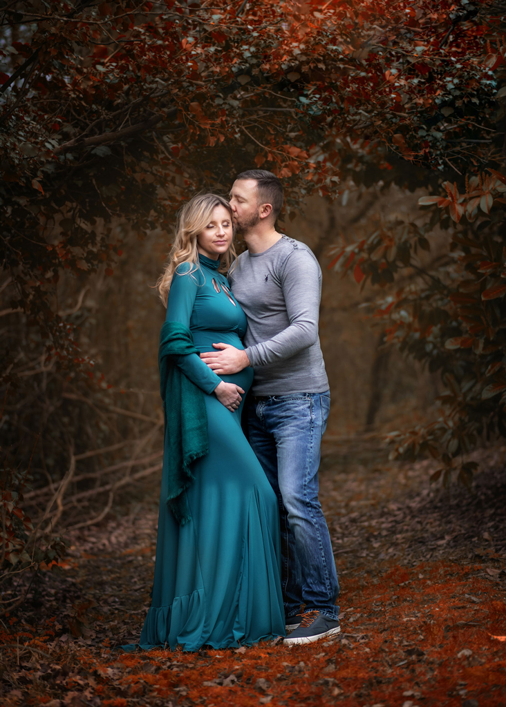 expecting couple posing in a Nottingham Park, pregnant mum is wearing a teal maternity dress