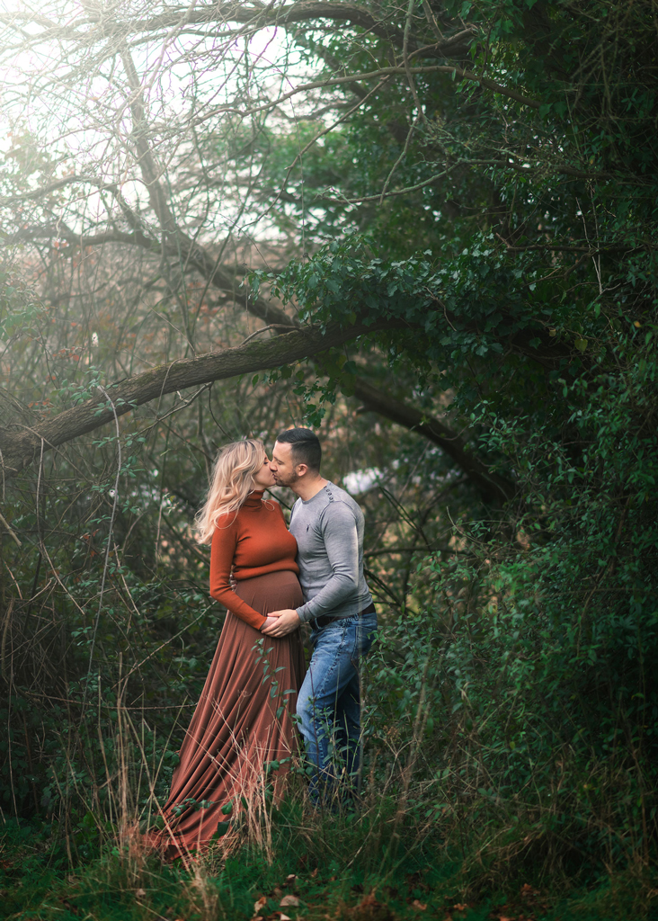 kissing couple in the park during maternity session in Nottingham