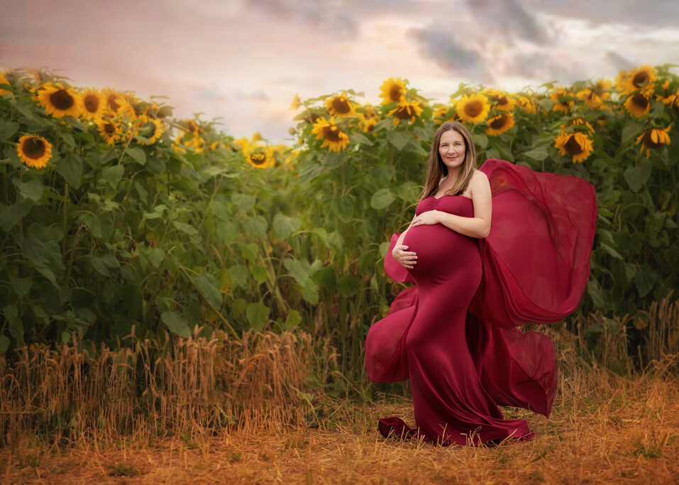 pregnant woman in Maternity red foalting dress posing on a sunflower field during maternity photo shoot in Nottingham