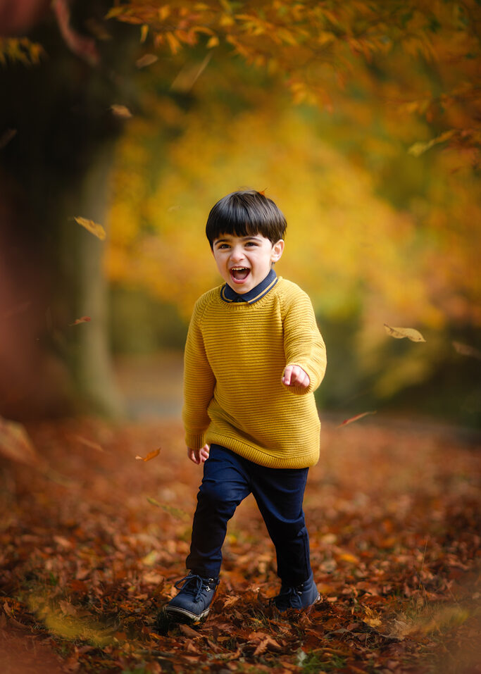 Autumn portrait if a boy with leaves in Wollaton Hall Park in Nottingham with family photographer