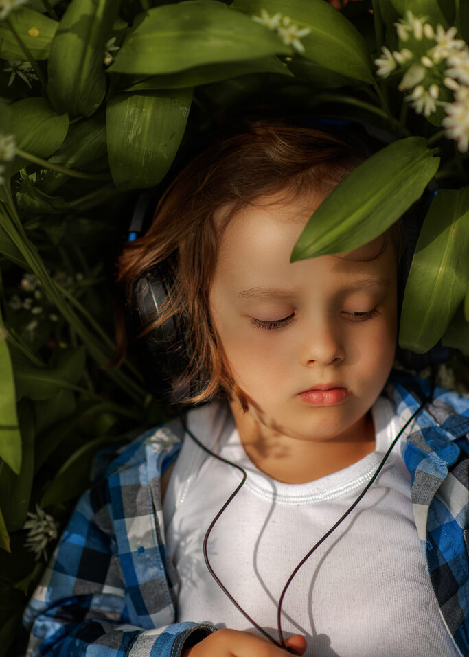 child laying on a ground in forest surrounded by wild garlic flowers with hearphones on, Children portrait photographer Nottingham, Derby, Eastwood, Giltbrook