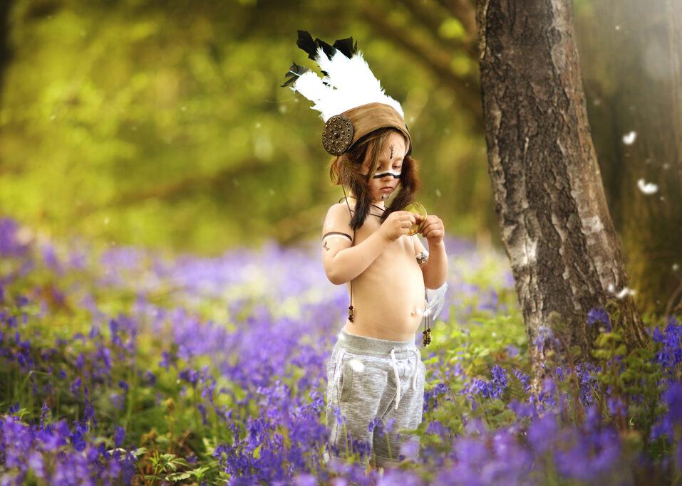 boy wearing indian headpiece in bluebells field, Nottingham children photographer