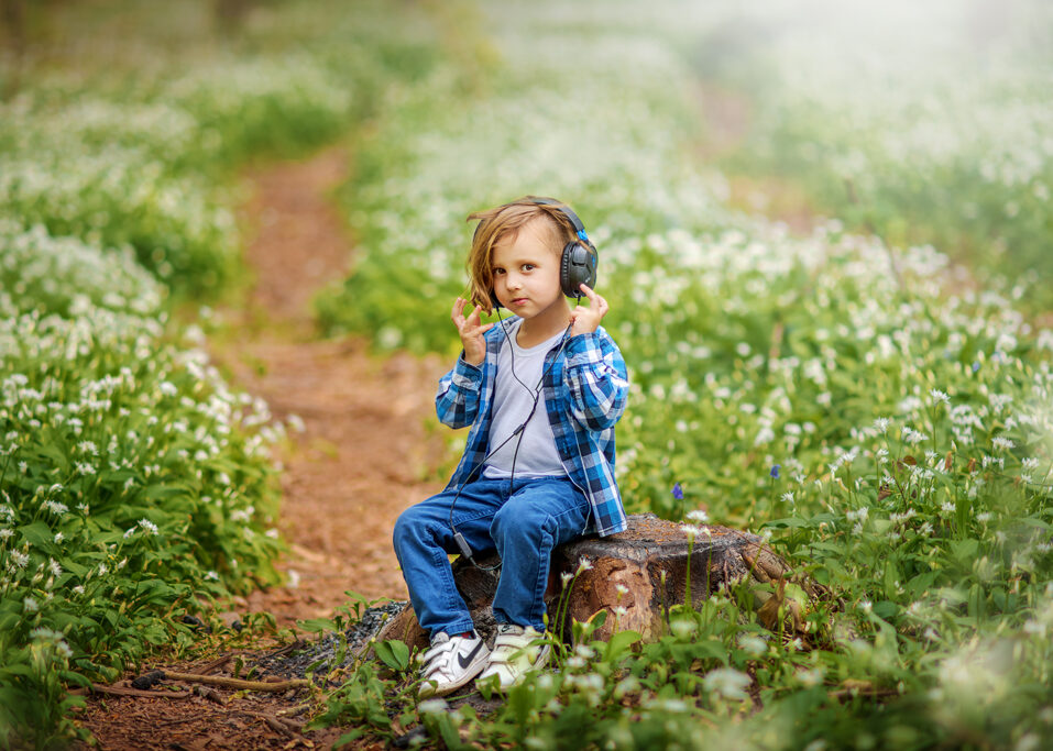 toddler-boy-sitting-on-a-tree-trunk-in-a-wild-garlic-field-family-outdoor-photoshoot-in-Nottingham-Derby-Mansfield